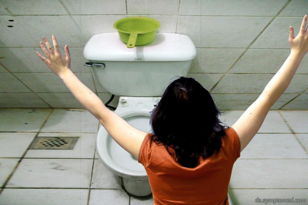Eine Frau bricht in die Toilette